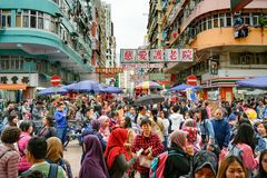Tr?ngde ihop gator i Kowloon, Hong Kong Lokala inv?nare och turister i gator av Kowloon royaltyfri foto