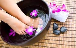 Tränkende Füße in der Schüssel duftendem mit Blumenwasser stockfoto