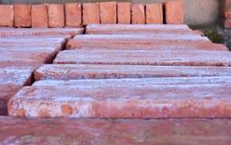 träpalettöverflöd av gamla staplade röda tegelstenar Tegelstenarna beställas i många rader arkivfoto