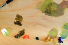 Träpalett med Olja-baserade målarfärger arkivbilder