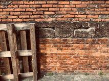 Träpaletter lutade framme av väggen för röd tegelsten royaltyfria foton