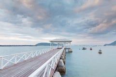 Träpaviljong och gångbana som leder till havet arkivfoton