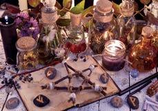 Träpentagram, öppen bok, glasflaskor, blommor, stearinljus och runor på häxatabellen royaltyfria bilder