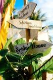 Träpilskyltar på strandsemesterorten Spindelhus Wahine strandstång arkivbilder