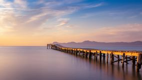 Träpir/brygga, playa de muro, Alcudia, soluppgång, berg, avskild strand, guld- solljus, reflexion, härlig himmel, fotografering för bildbyråer