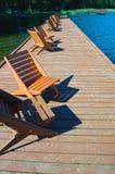 Träpir med en linje av stolar Fotografering för Bildbyråer