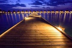 Träplankor i den Maldiverna ön till en bungalow på vattnet Royaltyfria Bilder