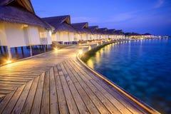 Träplankor i den Maldiverna ön till en bungalow på vattnet Fotografering för Bildbyråer