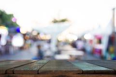 Träplankor med bakgrund är suddighet av ljus från utomhus- restaurang Arkivfoto