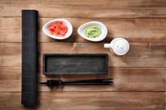 Träplatta för sushi med sås, ingefäran, wasabi och pinnar på tabellen arkivbilder