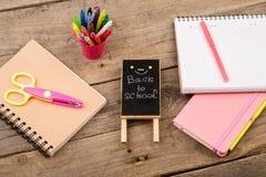 Träplatta med inskriften & x22; Dra tillbaka till school& x22; near notepads, sax och annan brevpapper på den bruna trätabellen arkivbild