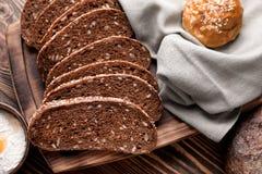 Träplatta med skivat nytt smakligt bröd på tabellen royaltyfri fotografi