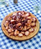 Träplattan av galicianen lagade mat bläckfisken med paprika- och olivnolla Arkivfoton