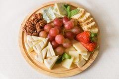 Träplattan med den läckra uppsättningen av ostar tjänade som med den organiska druvor, pecannötter, jordgubbar och mintkaramellen royaltyfri foto