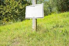 Träpol på en grön äng med tomt indikera för tecken fotografering för bildbyråer