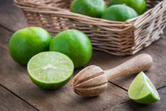 Träpress och limefrukt på tabellen arkivfoto