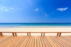 Träpryda eller däcka och tropisk strand royaltyfri bild