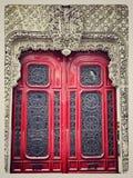 Träröd dörr för forntida tappning på stenen som bygger mycket härligt royaltyfri bild