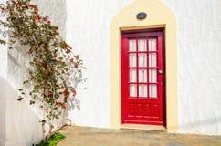Träröda dörrar och grön buske med den röda blomman över klar vit Royaltyfri Fotografi