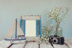 Träram för gammal tappning, vita blommor, fotokamera och segelbåt på trätabellen tappning filtrerad bild Royaltyfri Bild