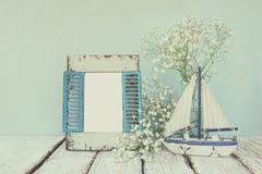 Träram för gammal tappning, vita blommor och segelbåt på trätabellen filtrerad och tonad bild för tappning Royaltyfria Foton