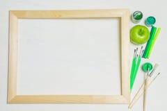 Träram med målarpenslar och det gröna äpplet Royaltyfri Fotografi