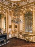 Trärum, stora speglar och ljuskrona på den Versailles slotten Arkivfoto