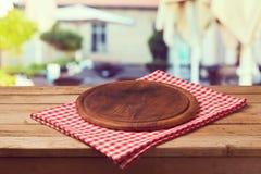 Trärunt bräde på bordduk över restaurangbakgrund Arkivfoto