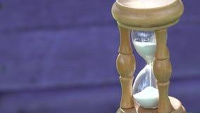 Träsandexponeringsglas med vit sand på suddig purpurfärgad wood bakgrund 4K arkivfilmer