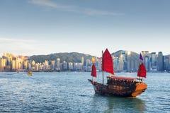 Träseglingskepp och den Hong Kong Island horisonten på aftonen arkivbild