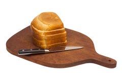 Träskärbräda med den skivade vitt bröd och kniven Arkivbilder