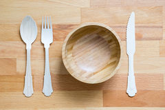 Träsked, gaffel, kniv och bunke på träbakgrund arkivbild