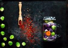 Träsked med kryddor och hemlagad sallad av sunda grönsaker i en glass krus på rostig metallbakgrund för tappning, kopieringsutrym Arkivbild
