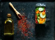 Träsked med kryddor och hemlagad sallad av sunda grönsaker i en glass krus på rostig metallbakgrund för tappning, Arkivfoto