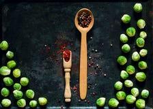 träsked med kryddor och nya brussels groddar på rostig metallbakgrund för tappning, grönsaker för sund matlagning, lekmanna- läge royaltyfri bild