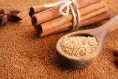 Träsked med pinnar och sött kanelbrunt socker Royaltyfri Fotografi