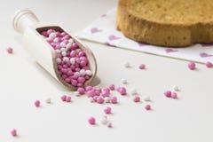 Träsked med rosa och vita anisbollar, holländska muisjes Och skorpa arkivfoto