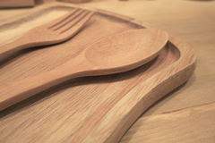 Träsked och gaffel som förläggas i träplattacloseup Royaltyfri Bild