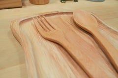 Träsked och gaffel som förläggas i träplattor Arkivbilder