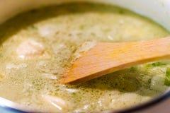 Träsked som rör hurtig grön krämig soppa Royaltyfria Foton