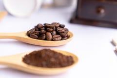 Träskedar fyllde med krossat jordkaffe på den vita backgroen arkivfoto