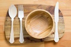Träskedar, gafflar och knivar i träbunke på träbackgro Royaltyfri Fotografi