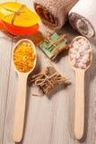 Träskedar med det gula och vita havet saltar och handgjord tvål f Arkivbild
