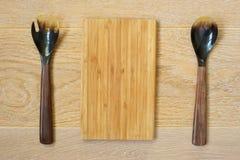 Träskedar och skärbräda på träbakgrund royaltyfri bild
