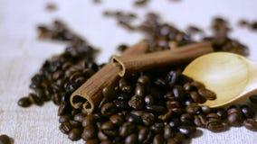 Träskedblandning bönorna för svart kaffe på gammal tygbakgrund arkivfilmer