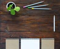 Träskrivbord för mörk brunt med Sketchbooksblyertspennaväxten Arkivfoto
