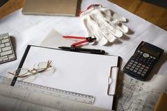 träskrivbordet med den öppna anteckningsboken, ritning rullade, lilla byn, calcul Royaltyfri Fotografi