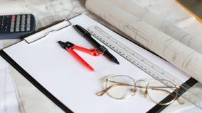 träskrivbordet med den öppna anteckningsboken, ritning rullade, lilla byn, calcul Arkivfoton