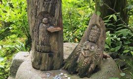 Träskulptur för två japan av en gudinna och en Buddha i en grön skog Royaltyfri Fotografi