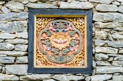 Träskulptur på en vaggavägg Arkivbild